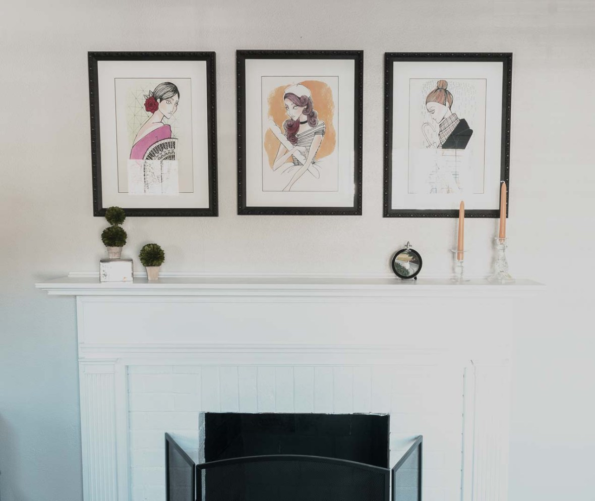 Three framed art prints by Stephanie above the fireplace.
