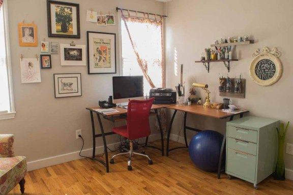 Stephanie's office has an L-shaped desk, a chair, yoga ball, small filing cabinet, and artwork on the walls.