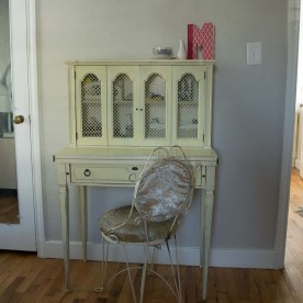 A pale yellow desk and a vintage white chair with satin upholstery.