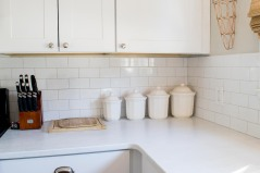 Four white canisters placed side by side against the back splash in the kitchen.