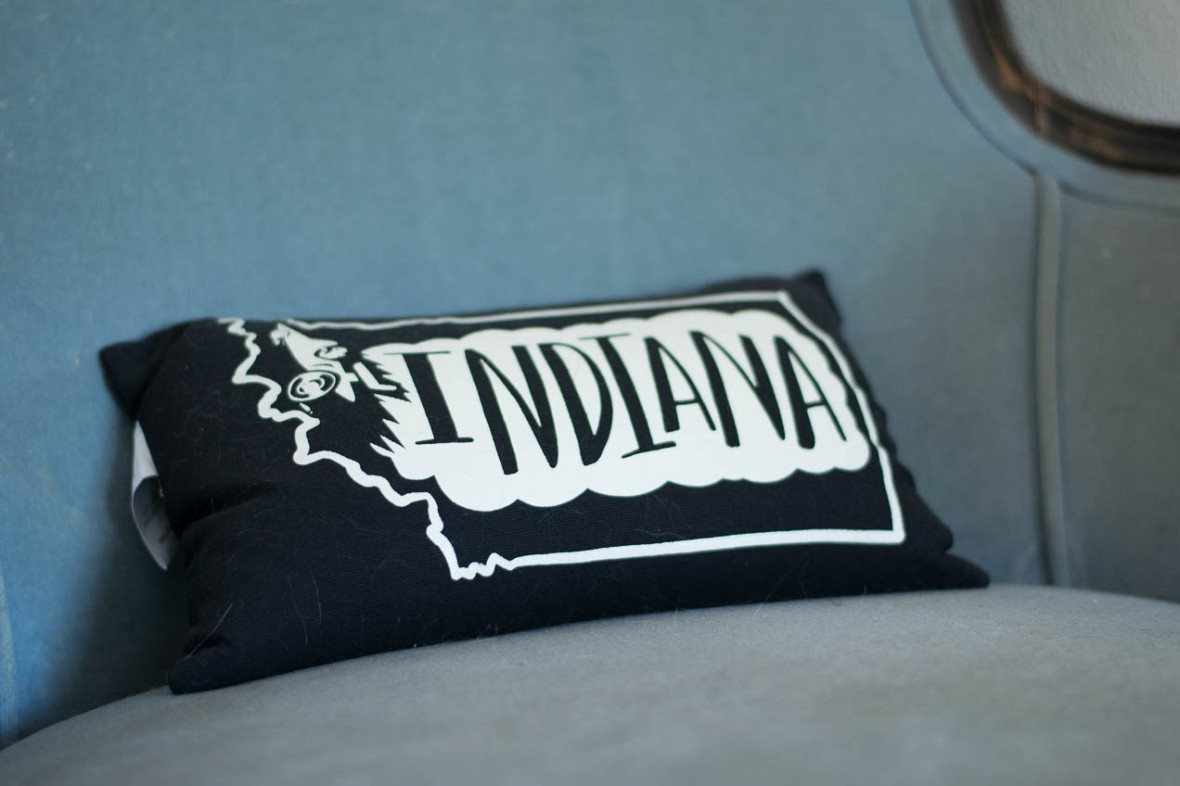 A small black and white decorative pillow with the outline of the state Indiana.