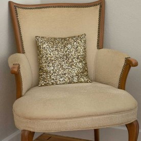 Vintage upholstered arm chair with a gold, glittery pillow.