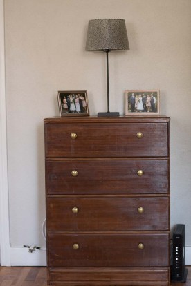 A chest of drawers in Stephanie's office on which sit two framed photos of their wedding.
