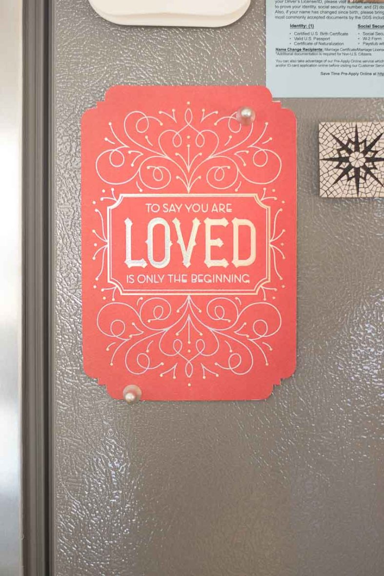 "A card on the refrigerator that reads, ""To Say You're Loved is Only The Beginning"""