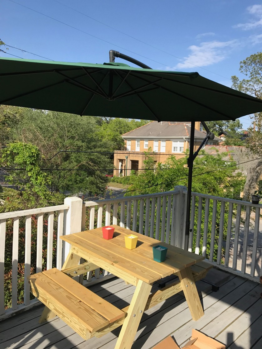 Balcony picnic table partially shaded by an outdoor umbrella.