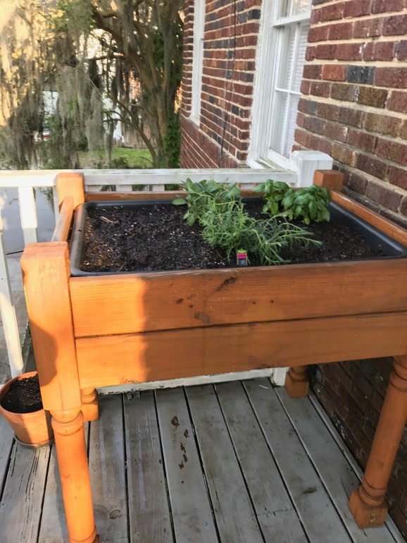 Small balcony garden in a raised wooden garden bed on four posts, holding a tub and herb garden.