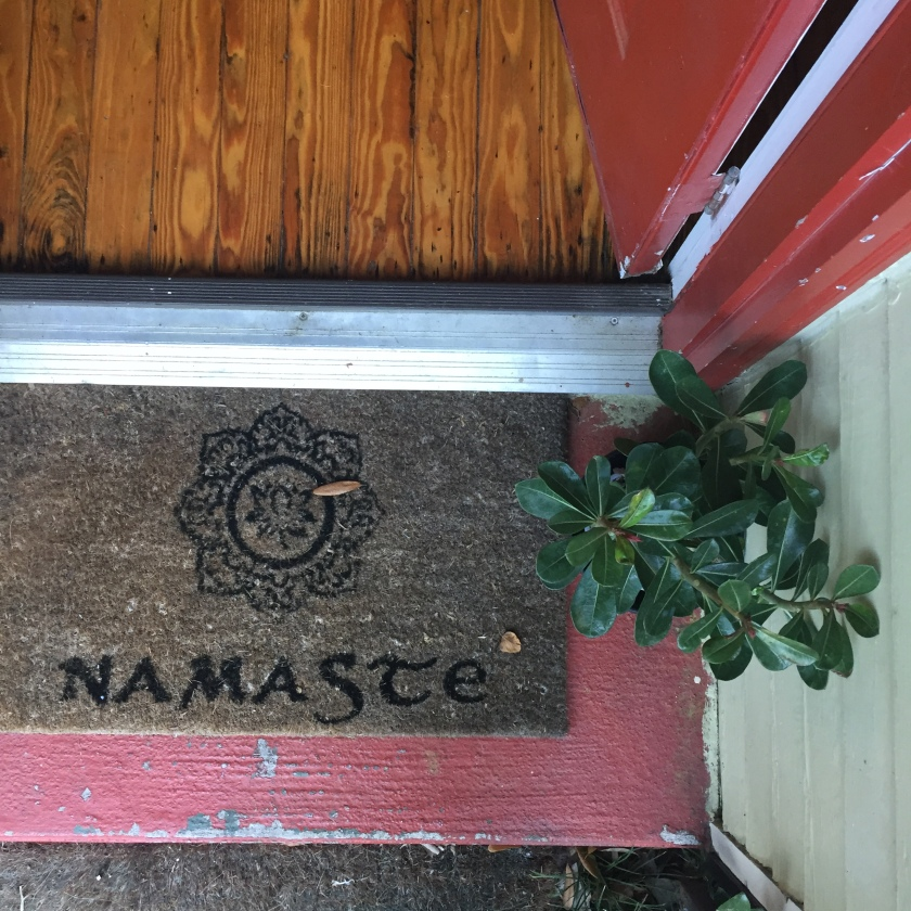 Welcome mat on a the doorstep from above next to a bonsai plant.
