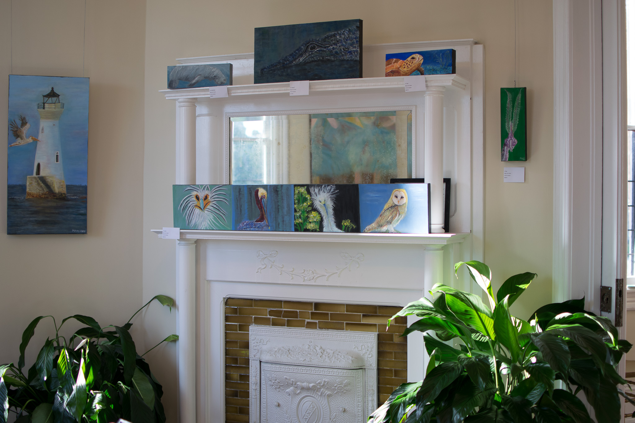 A photo of a room with art hanging on the walls and on the mantel of a fireplace.