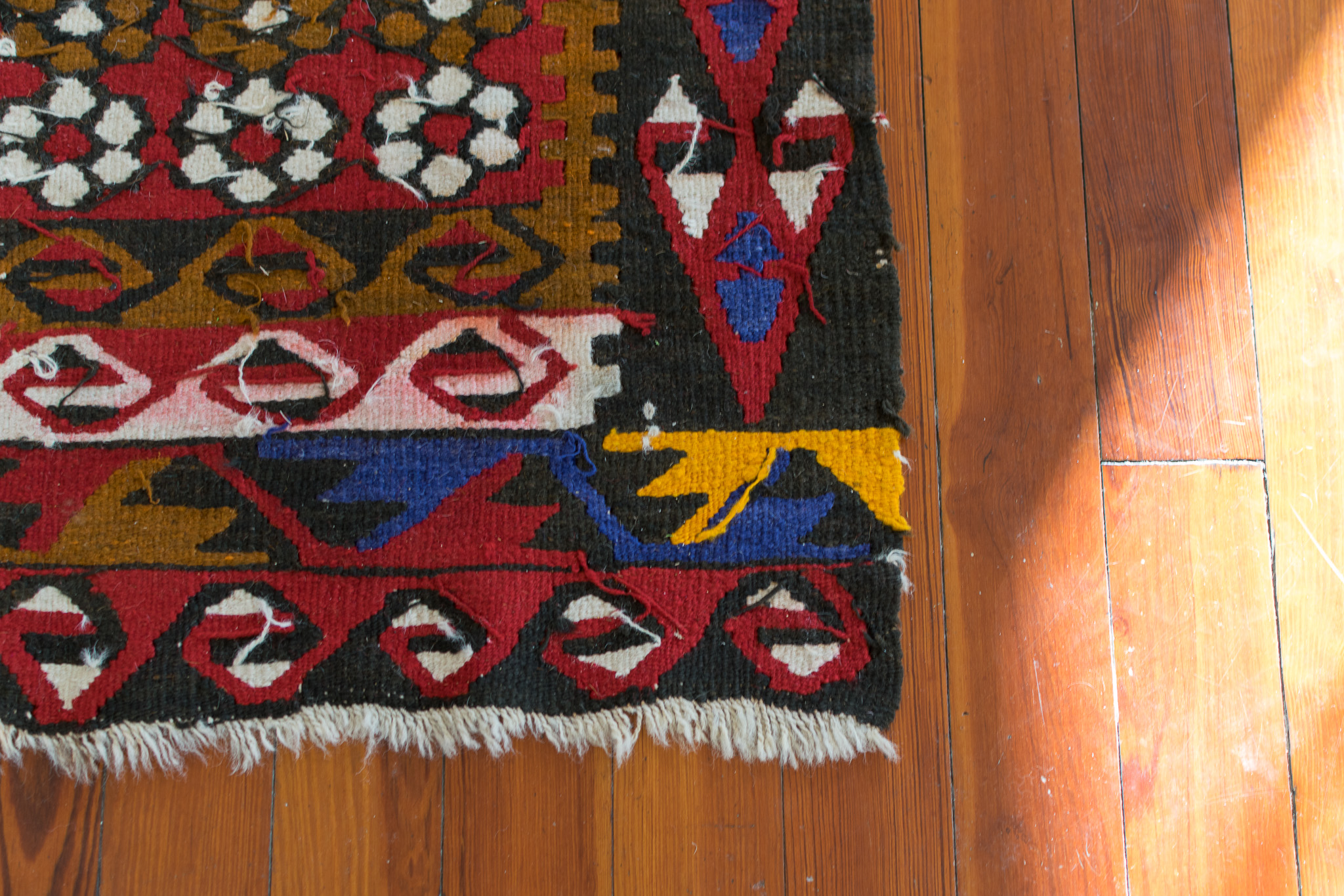 A photo of the corner patterned rug and the floor beneath it.