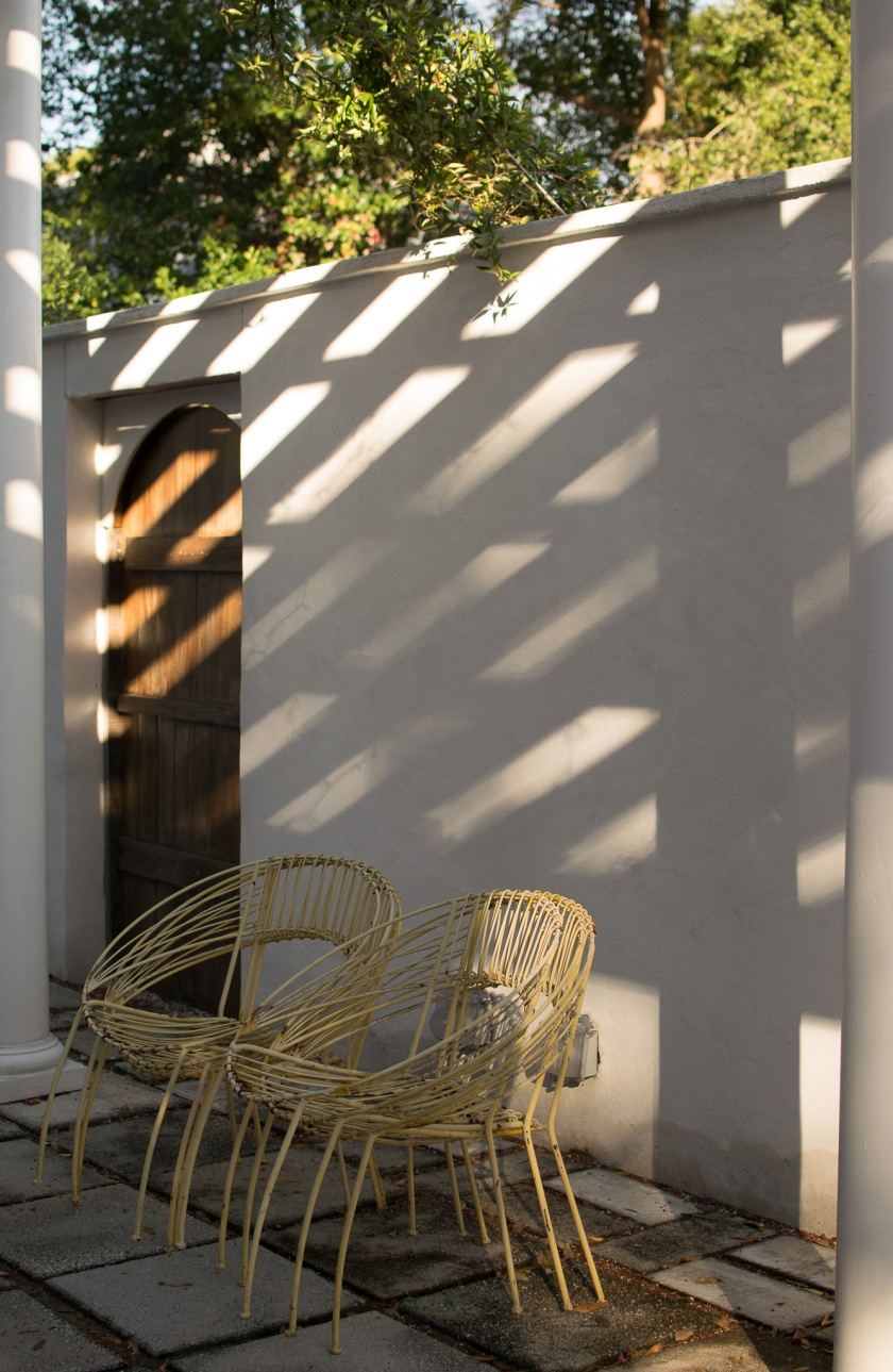 The pergola casts shadows on the courtyard wall in the background while fines hang overhead and vintage wire chairs sit in the foreground.
