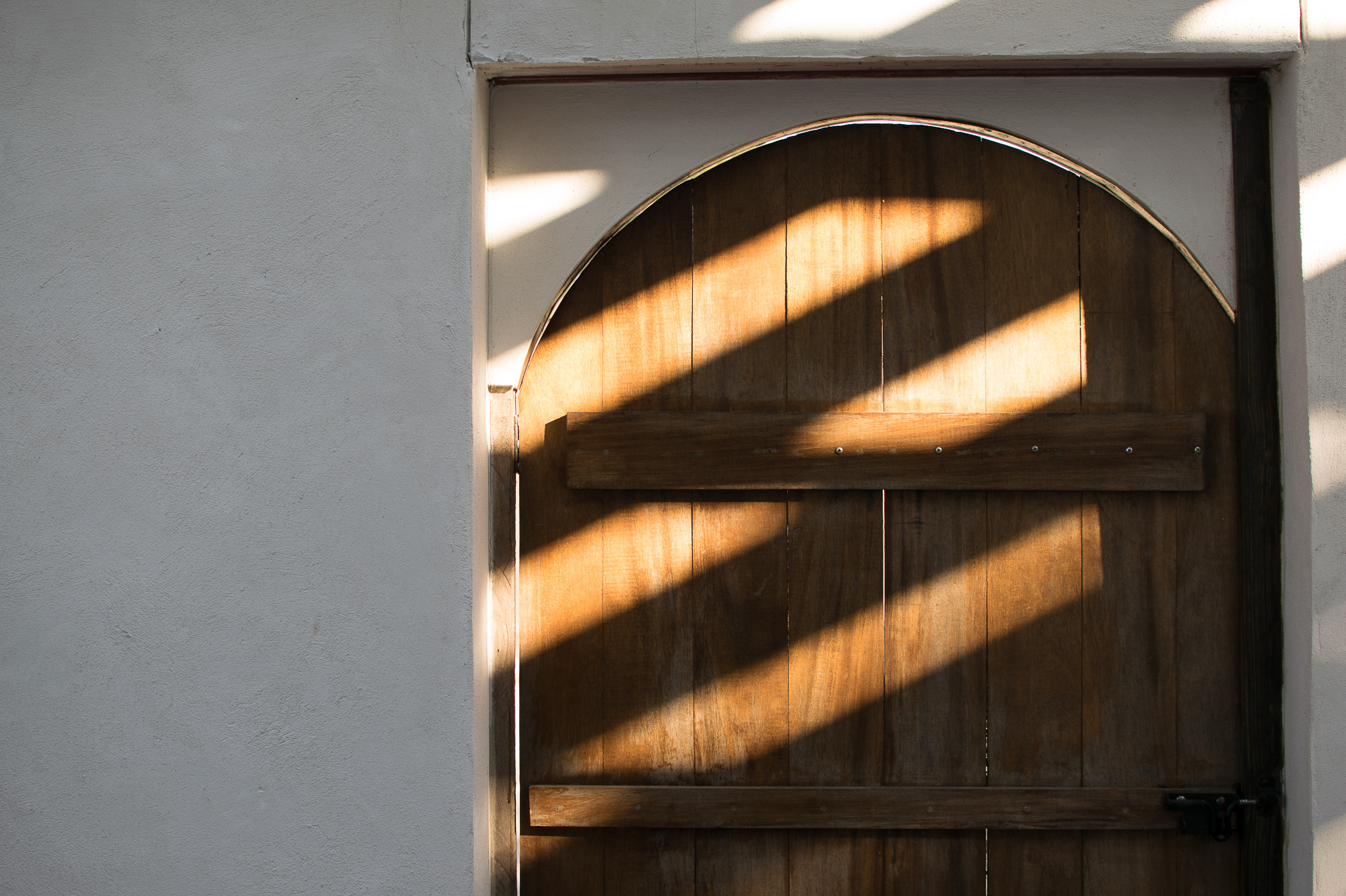 A partial photo of a wooden arched door and the stucco wall beside it.