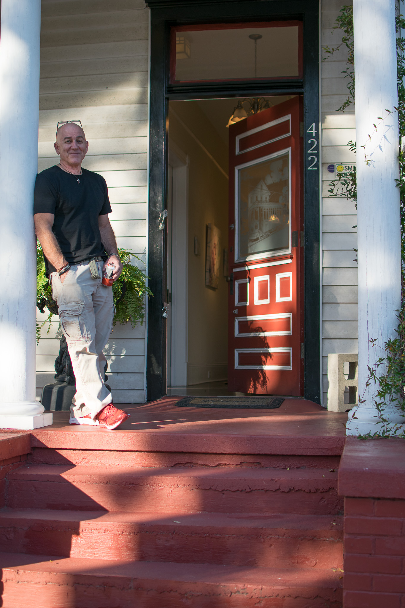 Thomas poses in front of the red front door atop of the red front steps.