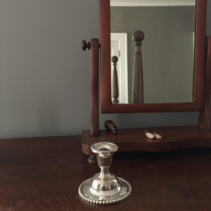 A mirror and a polished silver candle holder.