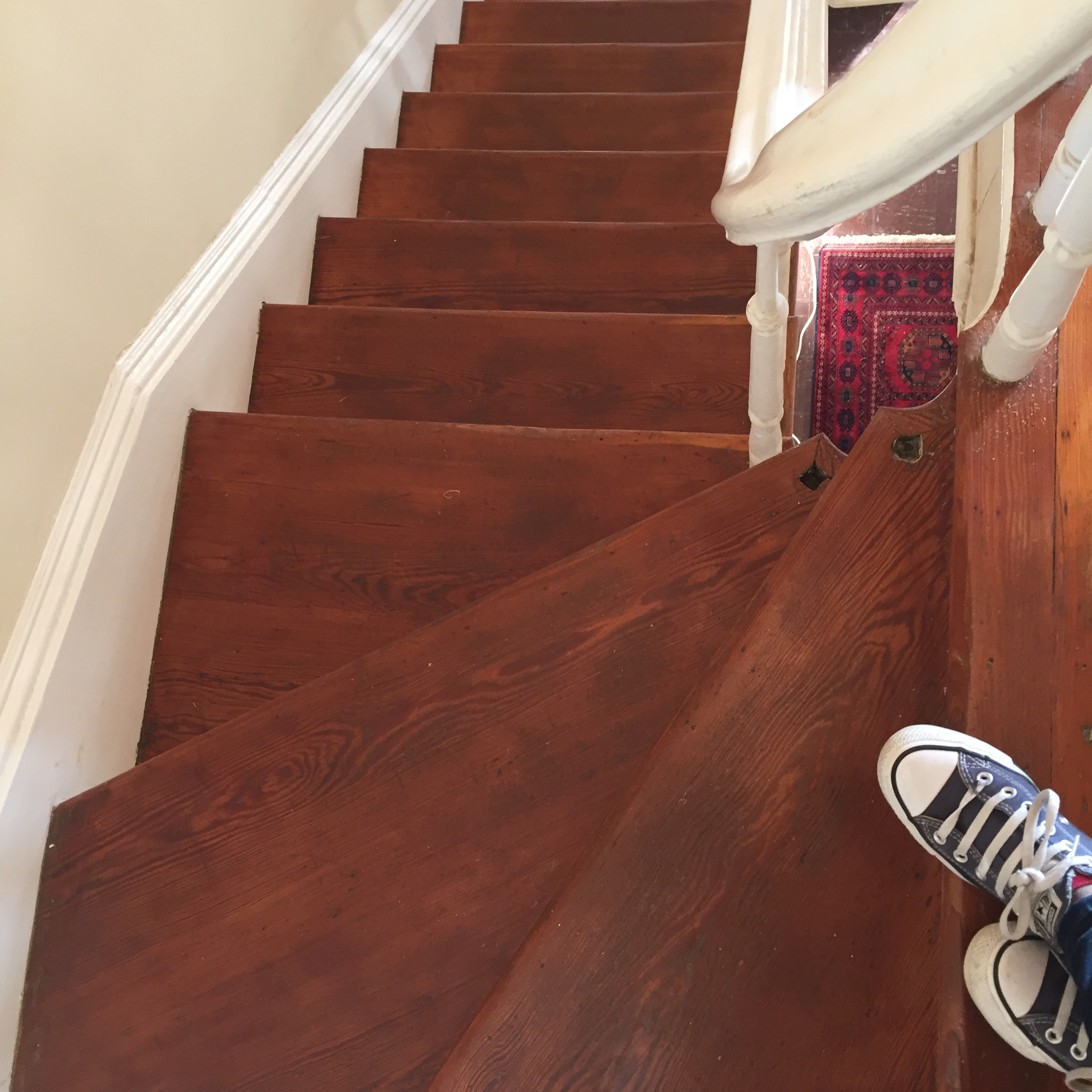 A picture of a slightly spiraled staircase from the top landing and two converse shoes.