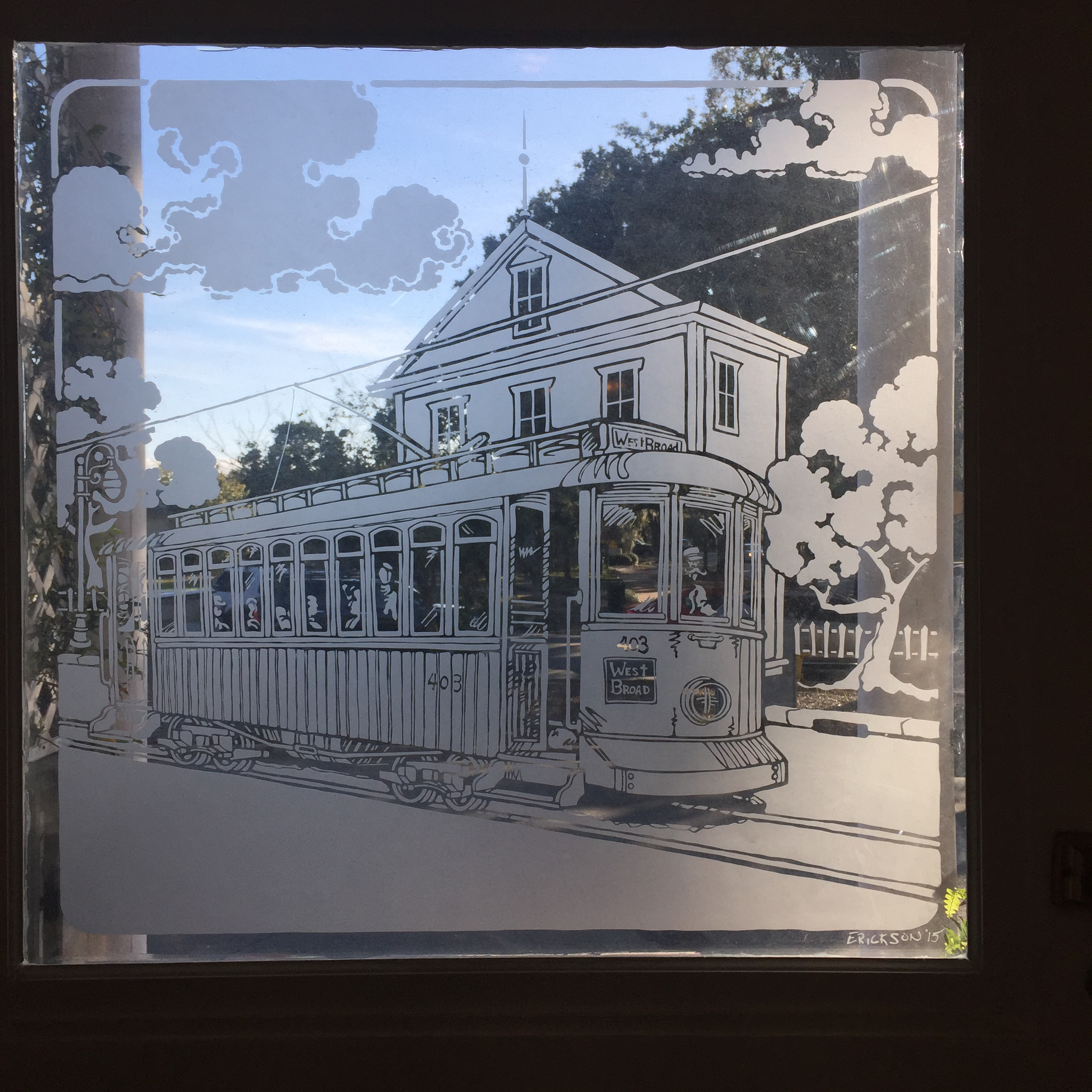 An etched pane on the front door shows West Broad Street in Savannah during the time of street cars.