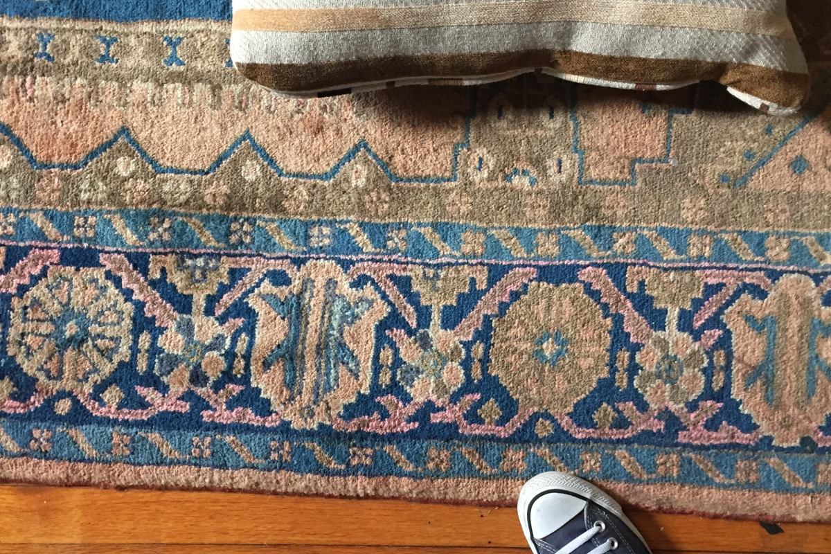 Overhead view of two converse shoes, a rug, and two pillows.