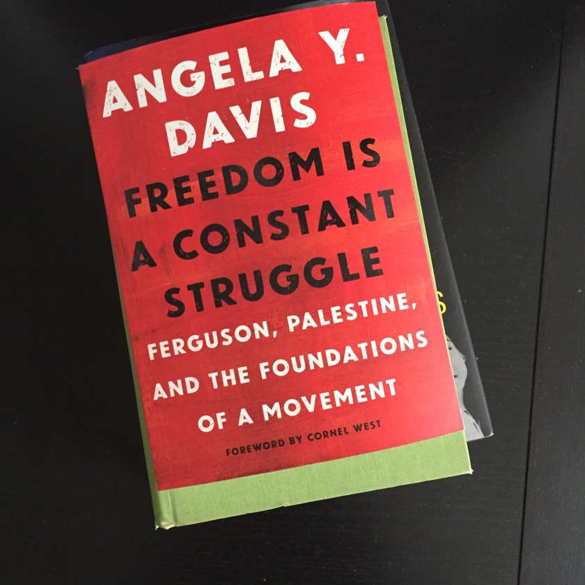 "An overhead photo of a stack of books. On top is Angela Davis' ""Freedom is a Constant Struggle"""