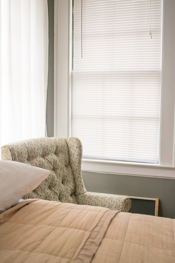 A view across the bed to the corner of the room where an upholstered chair sits between two windows.