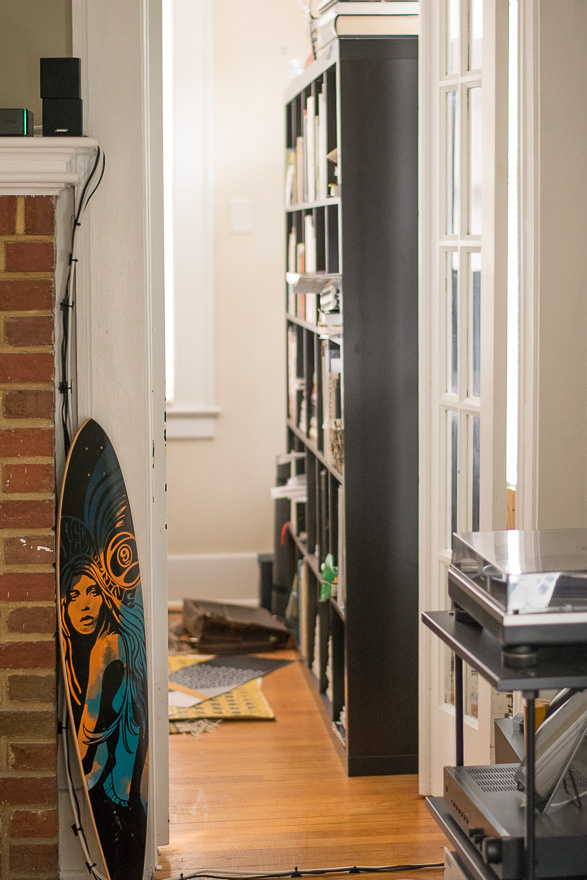 A look through to the library and a colorful longboard next to the fireplace.