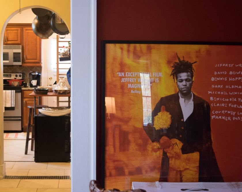 View of the wall next to the doorway to the kitchen from the dining room which has a big film poster of a Basquiat film.