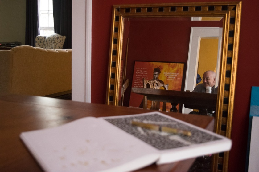 A photo through a mirror of Thomas at the dining room table and the film poster of Basquiat in the frame.